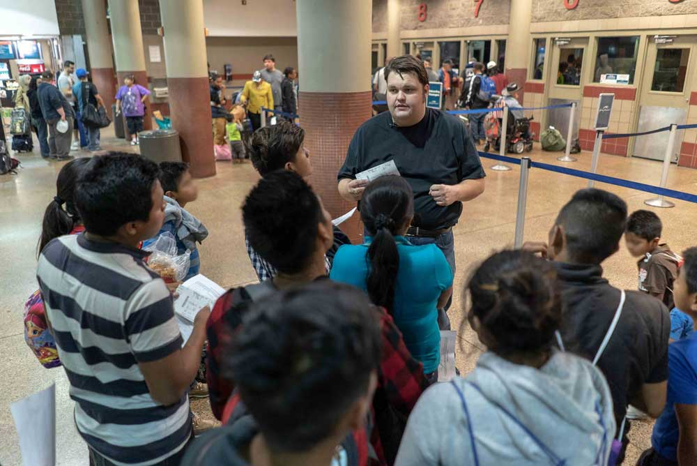 An IRC community engagement coordinator helping a group of refugees learn about travel and the airport. IRC/Andrew Oberstadt