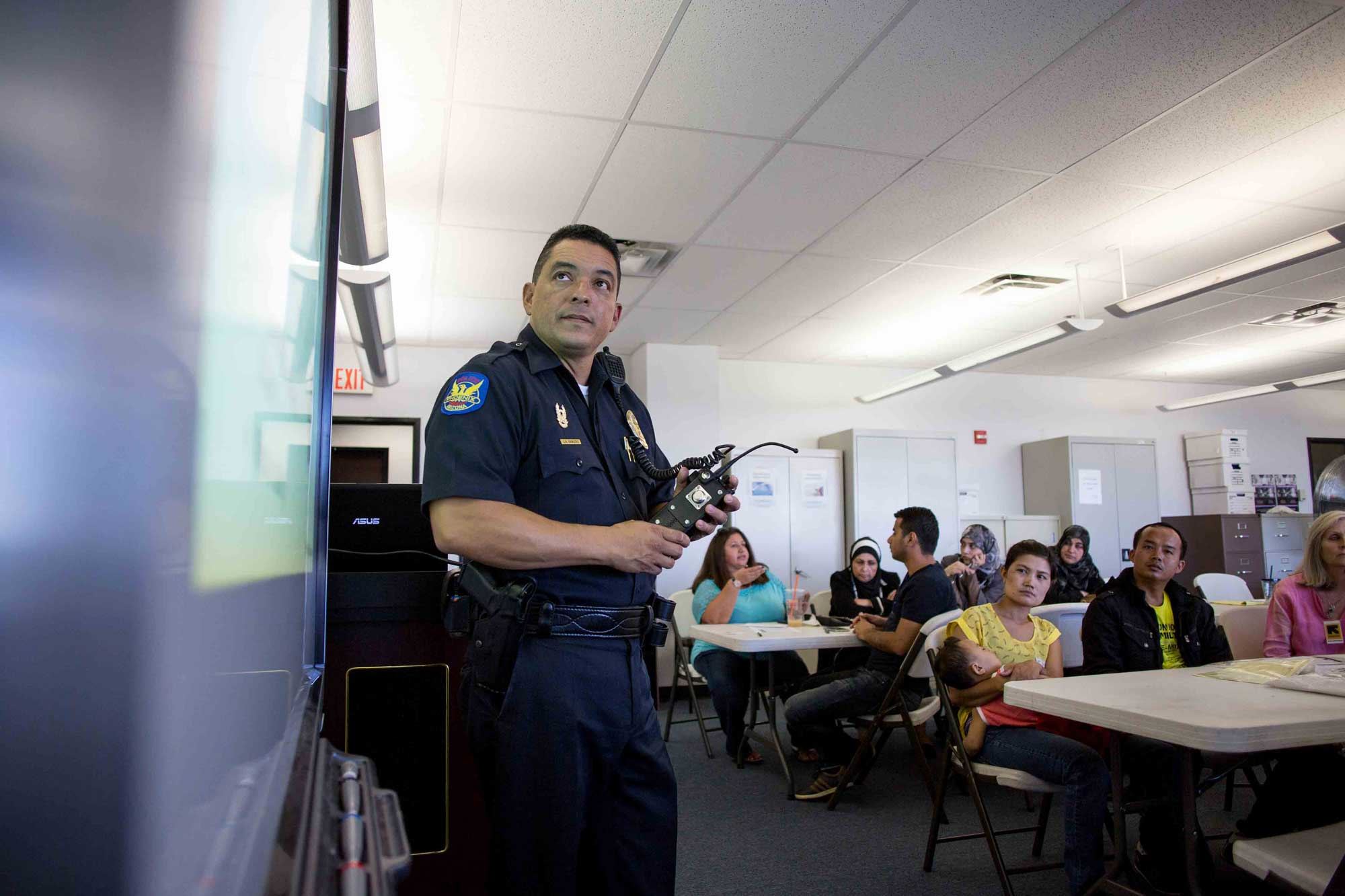 A police officer speaking to refugees about community services during a cultural orientation class