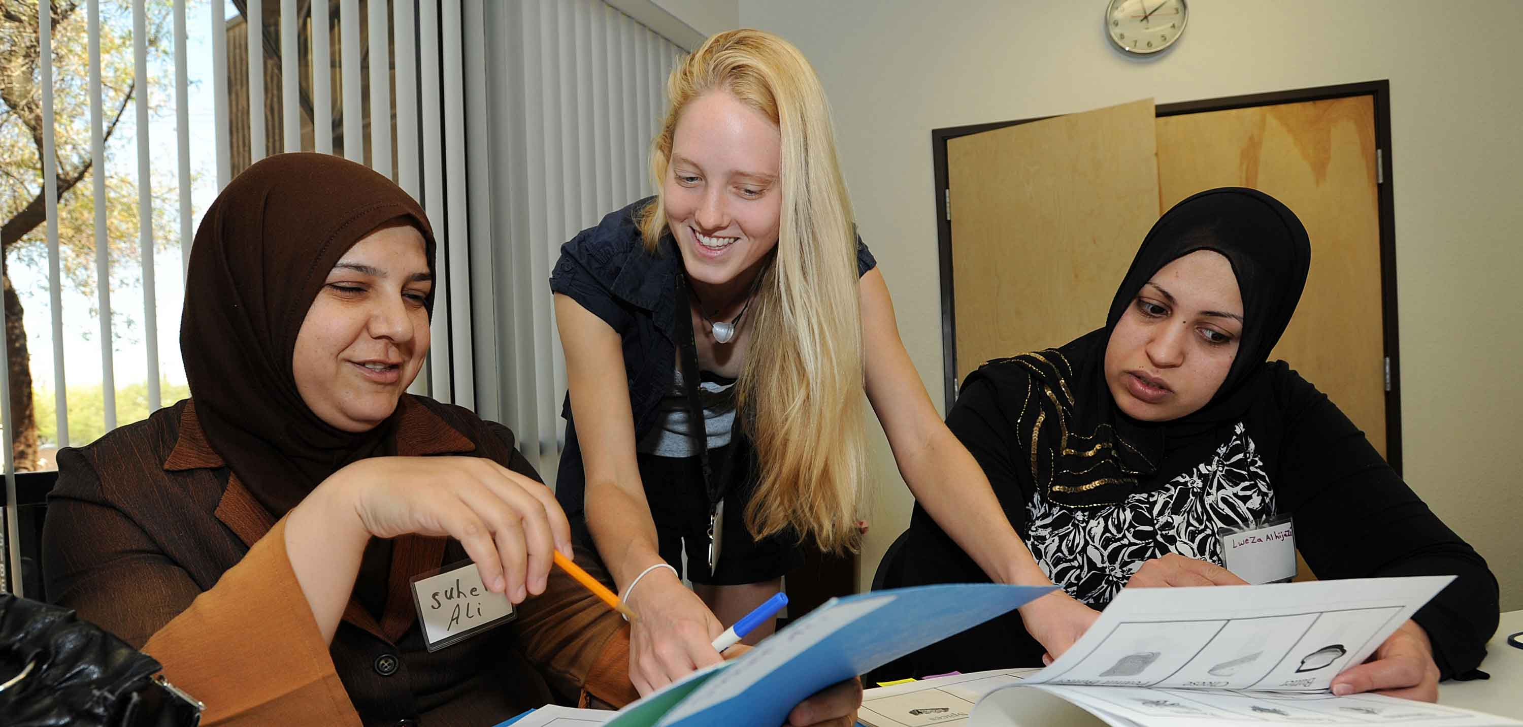A cultural orientation trainer teaching recently resettled refugees about U.S. culture