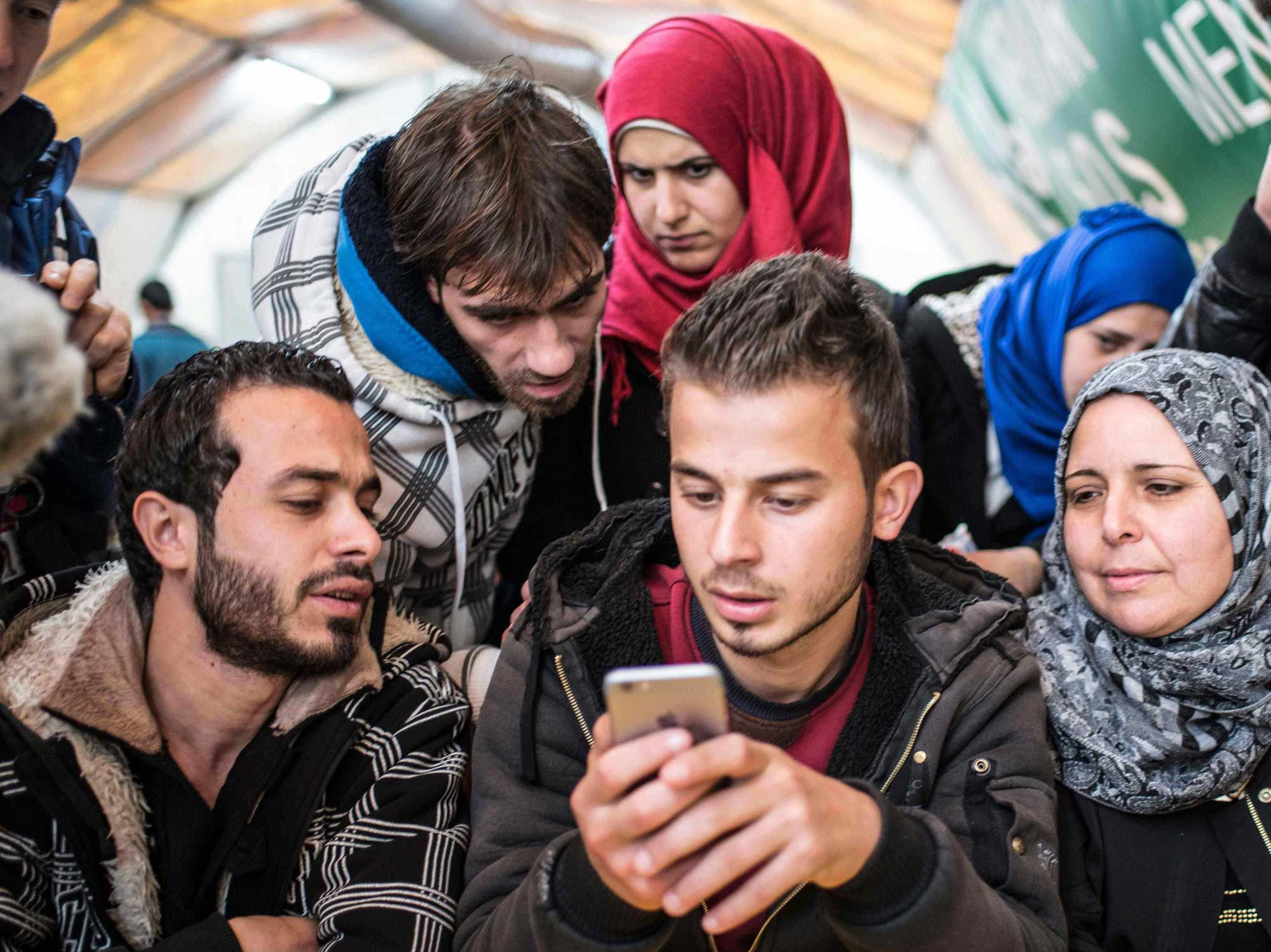 A Syrian refugee family looks at resources on a cell phone