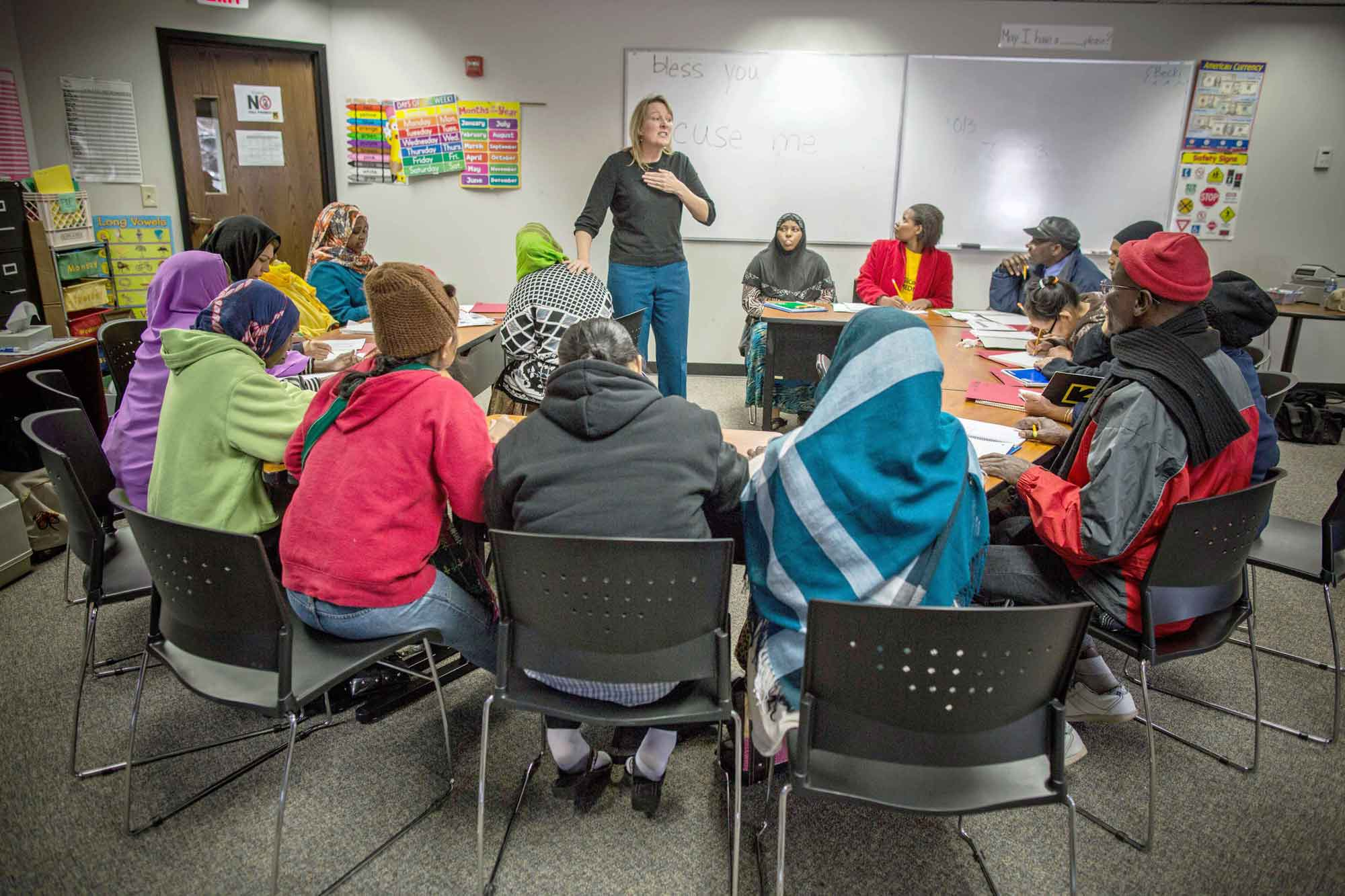 A cultural orientation trainer teaching a class of recently resettled refugees about U.S. cultural norms