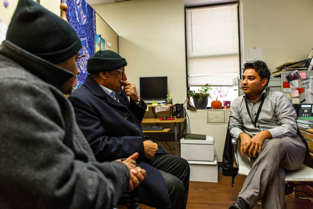 A refugee resettlement caseworker helping two recently resettled refugees at his office in Baltimore