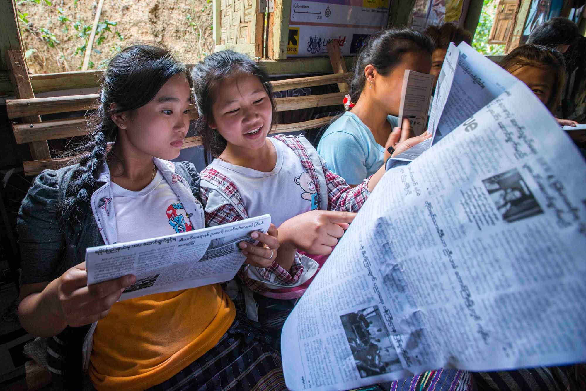 Burmese refugee young women reading the news at an IRC resource center in Myanmar