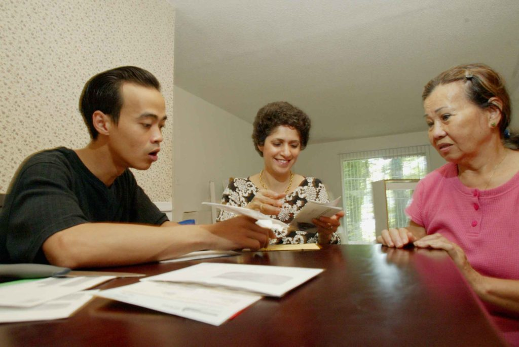 A cultural orientation trainer helping two refugees become acquainted to their new home after evacuating from Hurricane Katrina