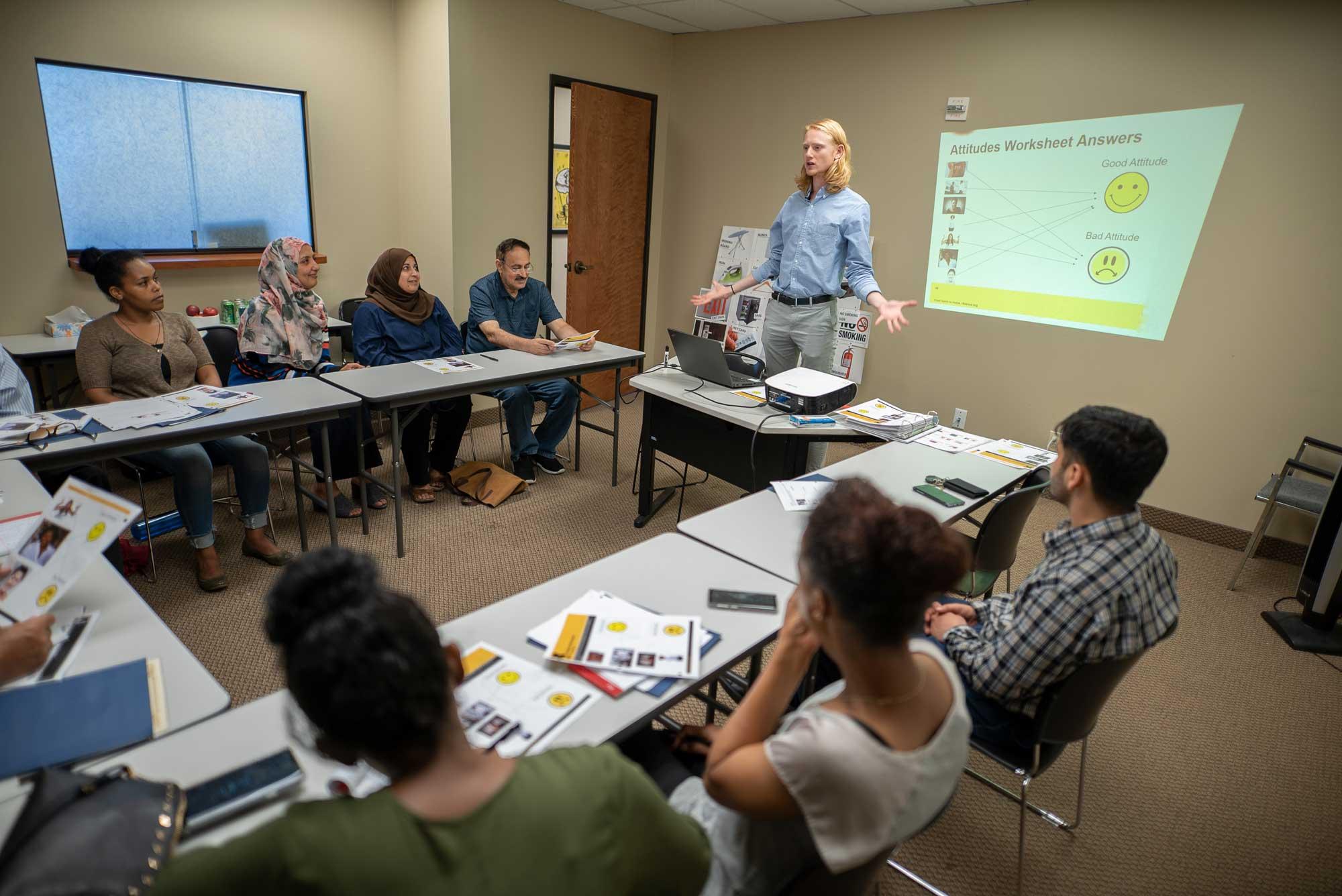 A cultural orientation provider teaching a class of refugees. IRC/AOberstadt