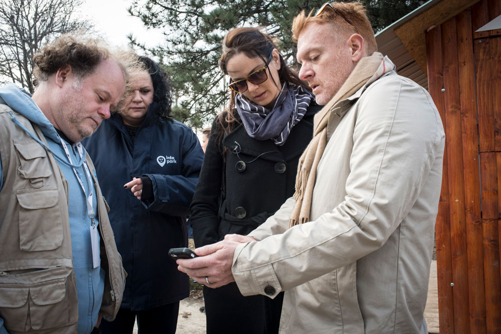 A man showing a group how to use a mobile phone. IRC/MJaques